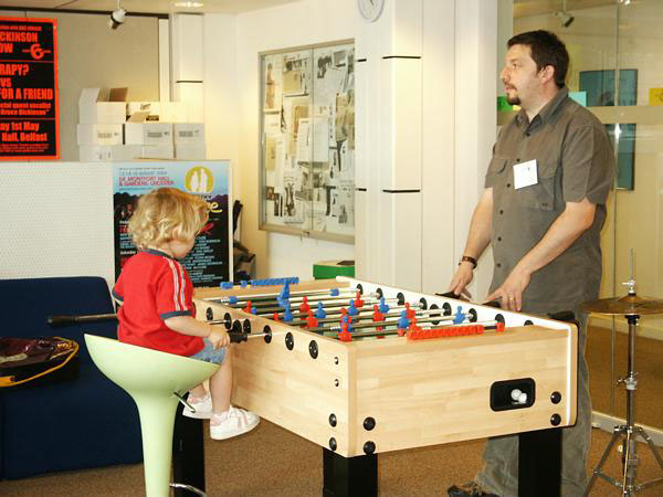 Miss Edie Pattison, learning how to play table football from her father